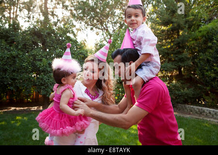 Family wearing party hats together in backyard - Stock Photo