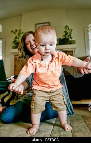 Caucasian mother helping baby walk on living room floor - Stock Photo