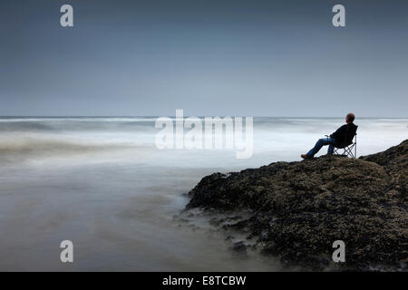 Caucasian man in chair overlooking waves on rocky beach - Stock Photo