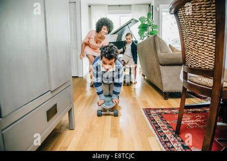 Mixed race family watching boy ride skateboard in living room - Stock Photo