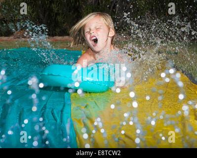 Caucasian boy playing on water slide - Stock Photo