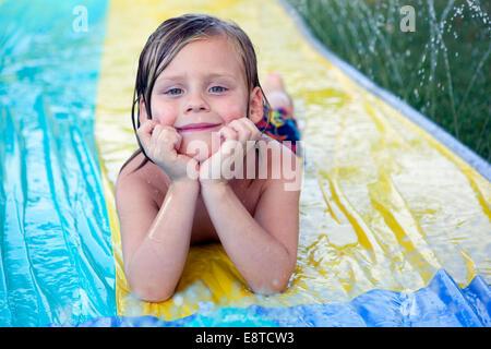 Caucasian boy smiling on water slide - Stock Photo