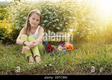 Caucasian girl sitting with basket of flowers - Stock Photo
