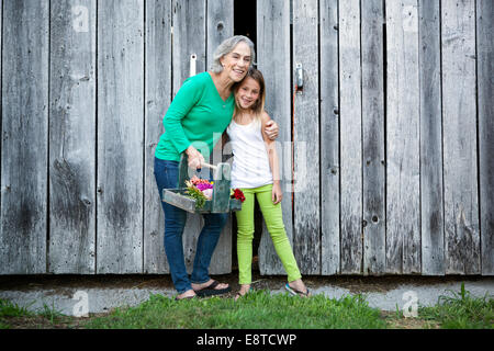 Caucasian grandmother and granddaughter smiling on farm - Stock Photo