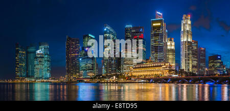 Skyscrapers in Singapore city skyline illuminated at night, Singapore - Stock Photo