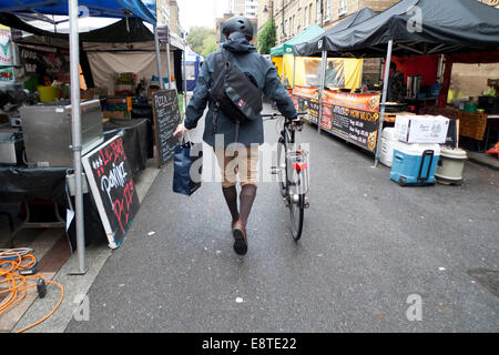 Barbican, London UK. 14th October 2014.  On a dry morning near the Barbican in the City of London a cyclist wearing - Stock Photo