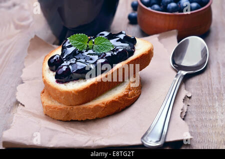 Toasted bread with blueberry jam on wooden table - Stock Photo