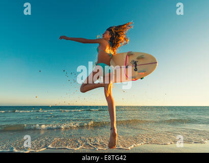 Young surfer running into the sea. - Stock Photo