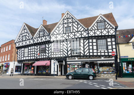 A row of shops in old black and white timber-framed buildings on the corner of Market Place in the historic town - Stock Photo