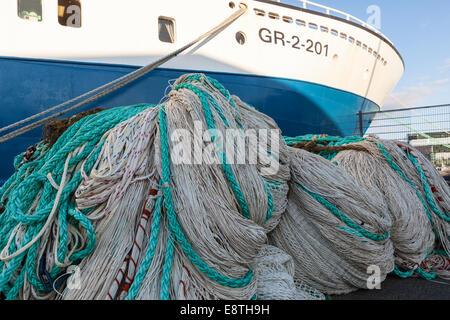 Fishing nets on quayside ready to loaded on board deep-sea trawler - Stock Photo