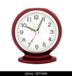 Red alarm clock with luminous hands after 10 am in a morning with alarm set at time 7 am to illustrate being late - Stock Photo
