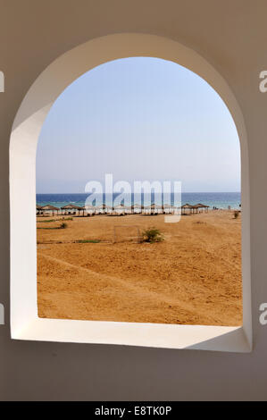 Looking through arched window at wide expanse of sandy beach to the sea - Stock Photo