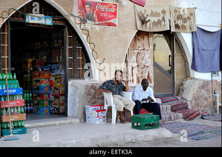 Two Egyptian shop keepers in front of stores, one selling groceries the other carpets - Stock Photo