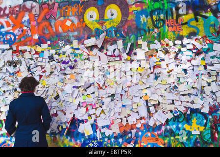 PRAGUE, CZECH REPUBLIC - SEPTEMBER 11, 2014: Woman looking at Famous John Lennon Wall on Kampa Island in Prague - Stock Photo