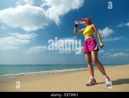 Fitness woman drinking water after running at beach. Thirsty sport runner resting taking a break with water bottle - Stock Photo