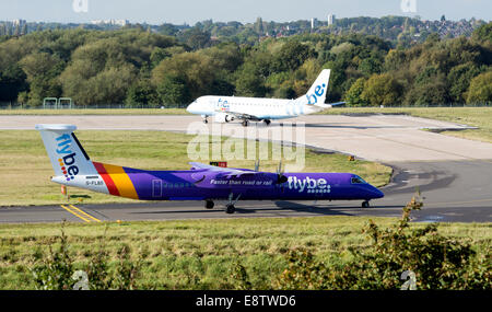 Flybe DHC Dash 8 and Embraer ERJ-170 aircraft taxiing at Birmingham Airport, UK - Stock Photo