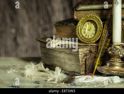 Old books, antique clock, candle in a candlestick and quill on wooden background. Vintage postcard. - Stock Photo
