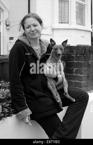 woman sitting on street wall holding a whippet puppy - Stock Photo