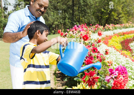 1 Indian Man Spraying Water with kid - Stock Photo