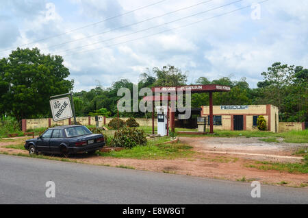 An abandoned gas station in south-west Nigeria reading 'RESCUE PETROLEUM' and a car wreck - Stock Photo
