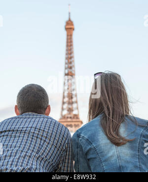 Rear view of a young couple looking to the Eiffel Tower in Paris. - Stock Photo