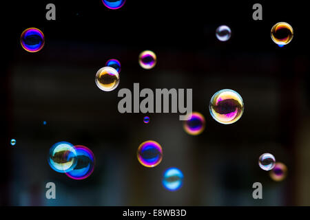 Atoms of Spring. Soap bubbles in the air against the dark background - Stock Photo