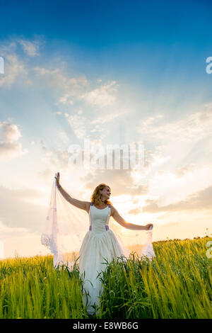 The runaway bride - a happy young woman girl in a wedding dress  standing in a field of yellow flowers evening - Stock Photo