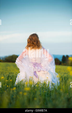 The runaway bride - a young woman girl in a wedding dress  standing confidently in a field of yellow flowers evening - Stock Photo