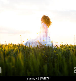 The runaway bride - a young woman girl in a wedding dress  standing in a field of yellow flowers evening sunlit - Stock Photo
