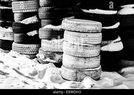 Tired And Retired. A view of a pile of used automobile tires in wintertime - Stock Photo
