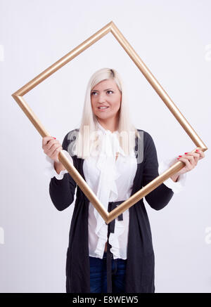 Portrait of a young blond woman holding a frame - Stock Photo