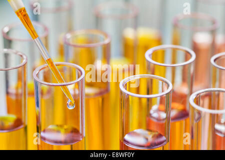 Close up of pipette dropping solution into test tube in rack in lab - Stock Photo