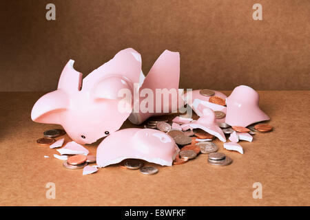 Broken piggy bank on counter - Stock Photo
