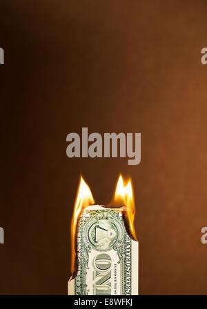 Folded dollar bill burning - Stock Photo