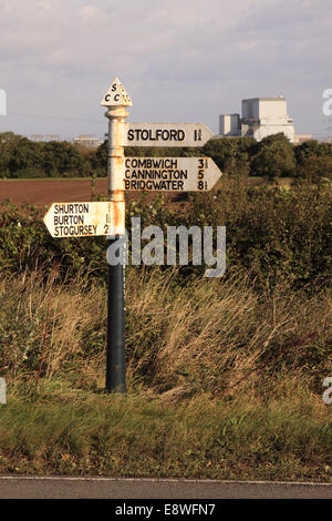 Hinkley Point nuclear power station in background with old road sign pointing to local villages Shurton Burton Stolford - Stock Photo