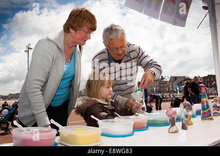 UK, England, Lancashire, Morecambe, Sandcastle Festival Freya from Carnforth doing sand art with grandparents - Stock Photo