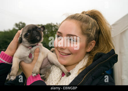 18 year old girl with her 13 week old pet dog - a Pug, Blackmoor, Hampshire, UK. - Stock Photo