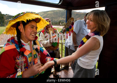 Andean Explorer, luxury train from Cusco to Puno. Train inside. Musicians and dancers in traditional costumes dancing - Stock Photo