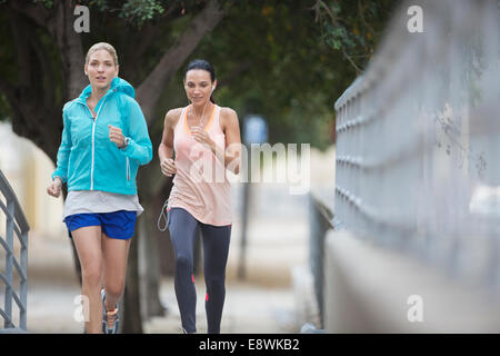 Women running through city streets together - Stock Photo