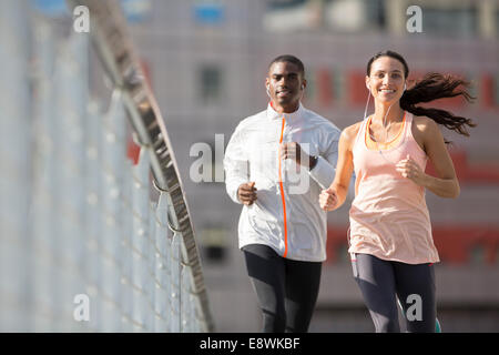 Friends running through city streets together - Stock Photo