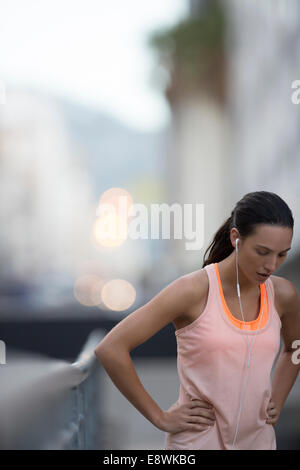 Woman resting after running on city street - Stock Photo