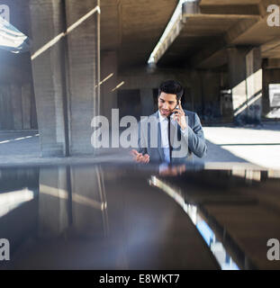 Businessman talking on cell phone in parking garage - Stock Photo