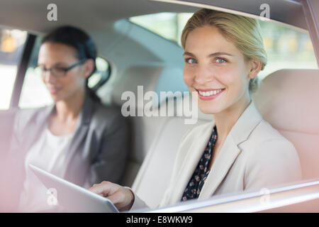 Businesswoman using digital tablet in car back seat - Stock Photo