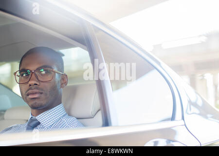 Business man sitting in car back seat - Stock Photo