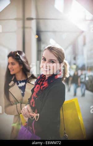 Women walking together down city street - Stock Photo