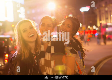 Women laughing together on city street - Stock Photo