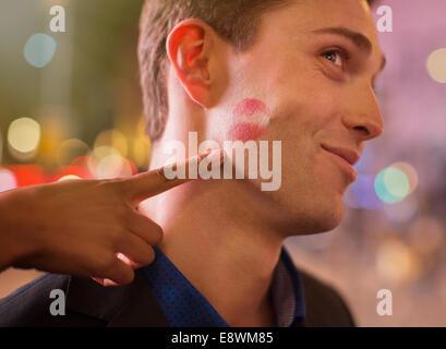 Man posing with lipstick print on cheek in city - Stock Photo