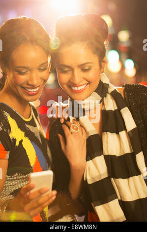 Women looking at cell phone together on city street at night - Stock Photo