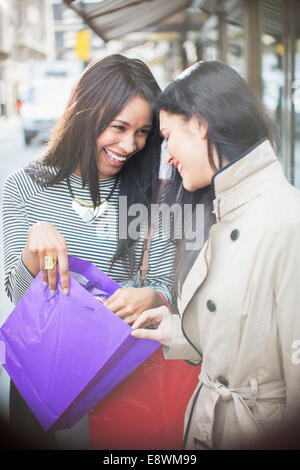 Women looking through shopping bag together on city street - Stock Photo