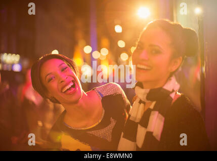 Friends laughing together on city street at night - Stock Photo